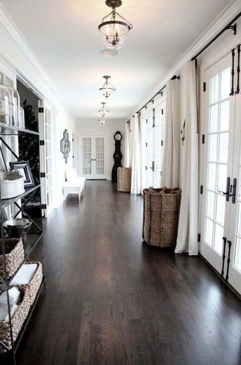 a neutral space with a dark hardwood floor that makes it look expensive and very stylish, and baskets add coziness