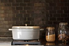 14 rich-toned cabinets, grey stone countertops and black subway tiles for the backsplash make up a vintage kitchen