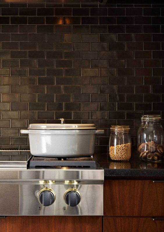 rich-toned cabinets, grey stone countertops and black subway tiles for the backsplash make up a vintage kitchen