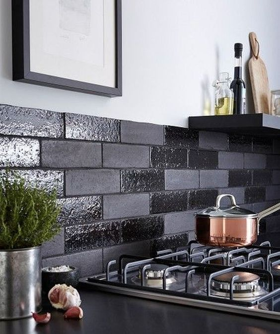 a black backsplash done with shiny and matte faux bricks is a cool and fresh modern idea to try