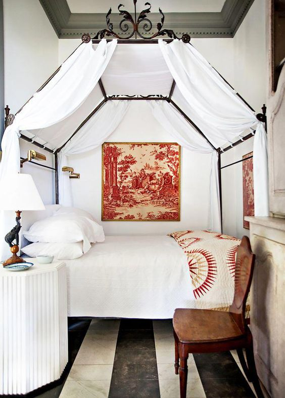 a cozy vintage bed with white curtains and beautiful forged decor on its top makes the bedroom refined