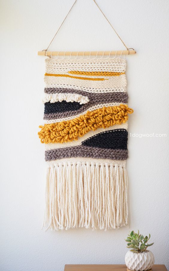 a crochet wall hanging in neutrals, mustard and black looks catchy and cool