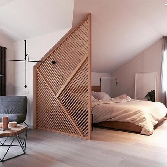 a geometric wooden screen highlights the attic ceiling of the bedroom and adds interest and geometry to the space