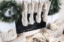 15 a magical fireplace with knit stockings, evergreen wreaths, a greenery runner and fluffy pillows and lights