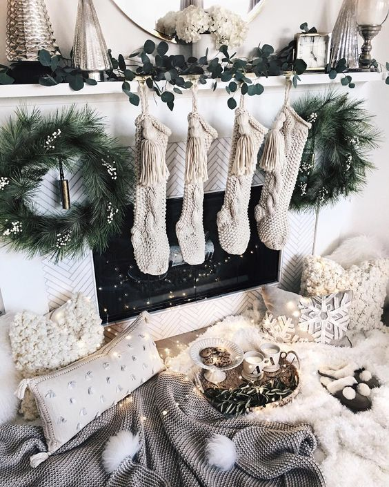a magical fireplace with knit stockings, evergreen wreaths, a greenery runner and fluffy pillows and lights