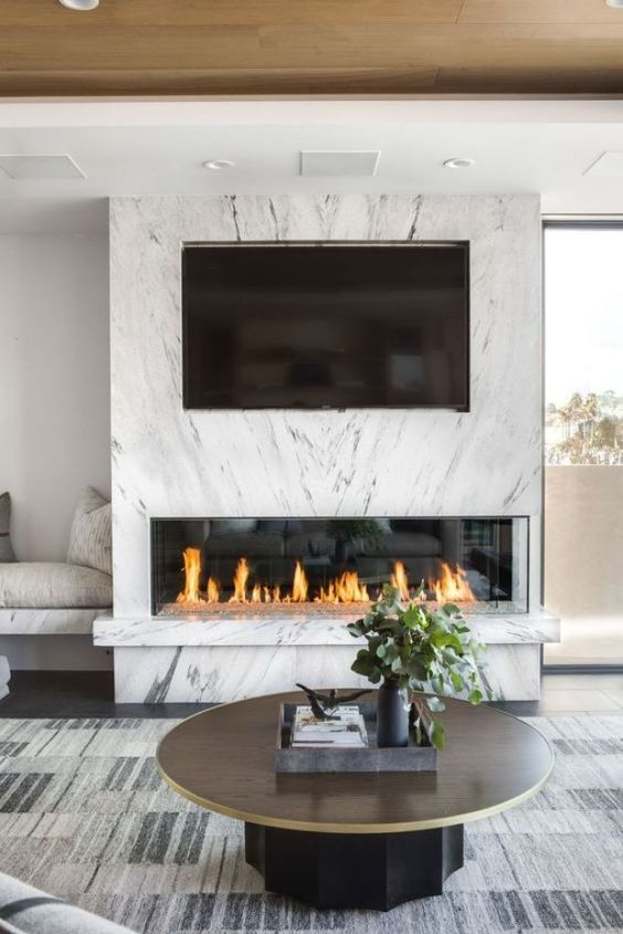 a minimalist fireplace enclosed into marble looks refined, chic and gorgeous and gives an edgy feel to the space