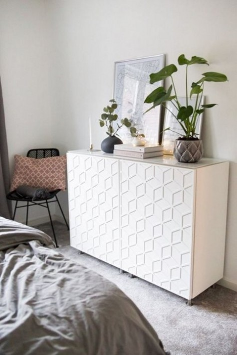 an IKEA Metod cabinet decorated with modern and bold front decor panels is a cool idea for a contemporary bedroom