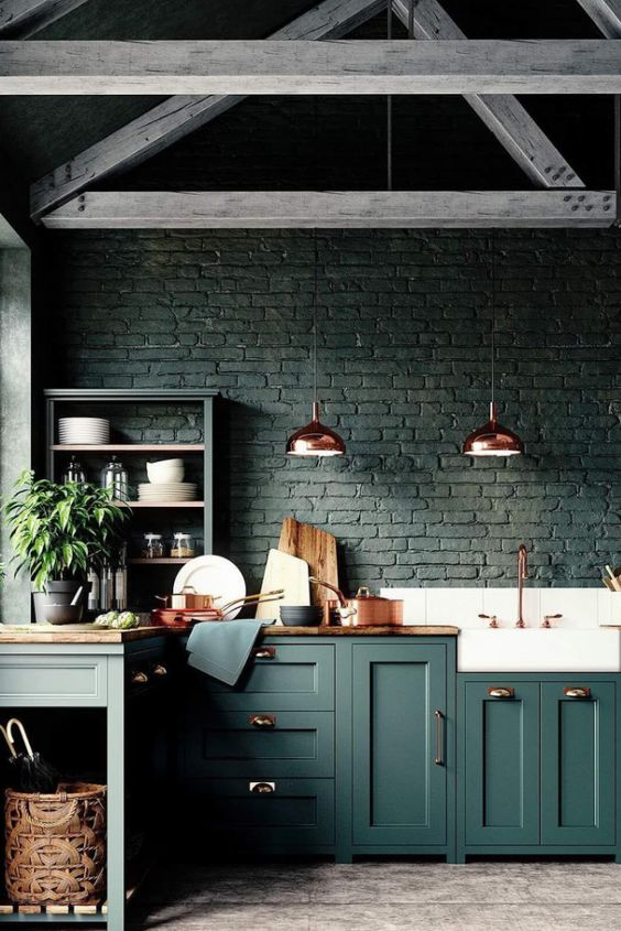 a black brick backsplash matches the forest green cabinets and wooden countertops creating a moody feel in the space