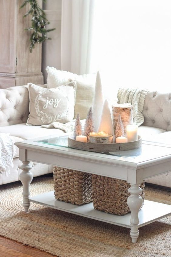 a neutral living room with white winter pillows, a tray with snowy Christmas trees and candles looks cute and chic