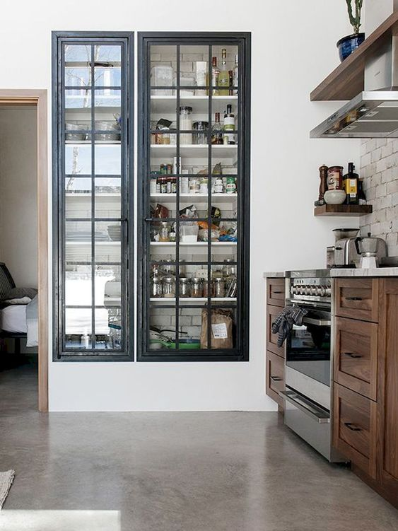 a built in pantry with framed glass doors that keep it in order but allow you see what's inside
