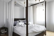 17 a dark stained canopy bed with light fabric and lots of bulbs hanging on it for additional light and to make the space more welcoming