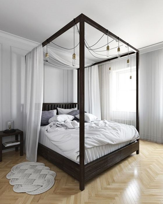 a dark stained canopy bed with light fabric and lots of bulbs hanging on it for additional light and to make the space more welcoming
