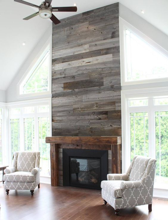 a grey reclaimed wood wall with a built-in fireplace is a warming up idea for a living room