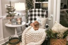 17 a neutral nook with a chunky knit blanket, evergreens and a Christmas tree with lights, baskets and berries plus a buffalo check chair