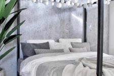 18 a black canopy bed with white bulb garlands over it is a fun idea to add light without any lamps around