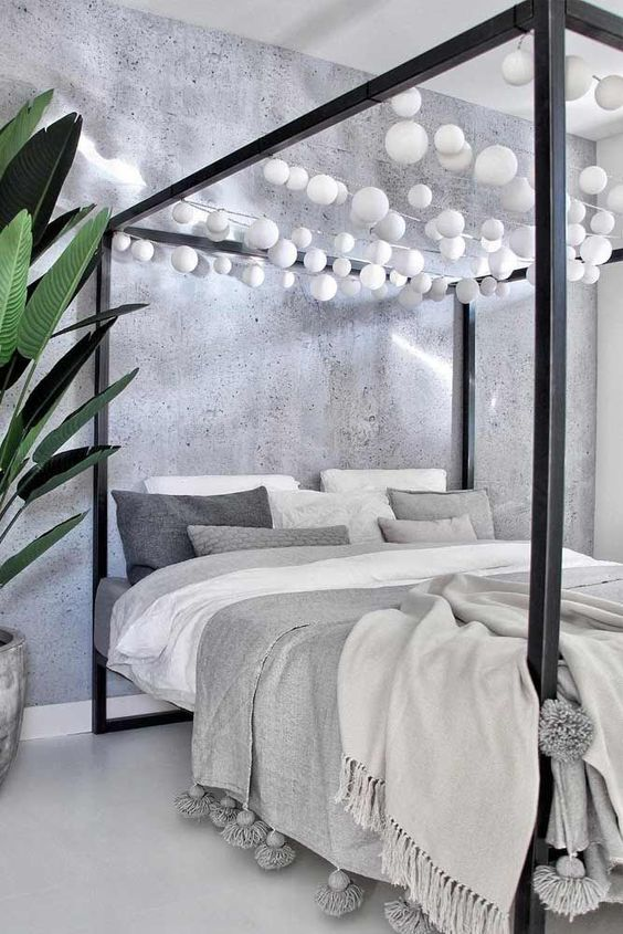 a black canopy bed with white bulb garlands over it is a fun idea to add light without any lamps around