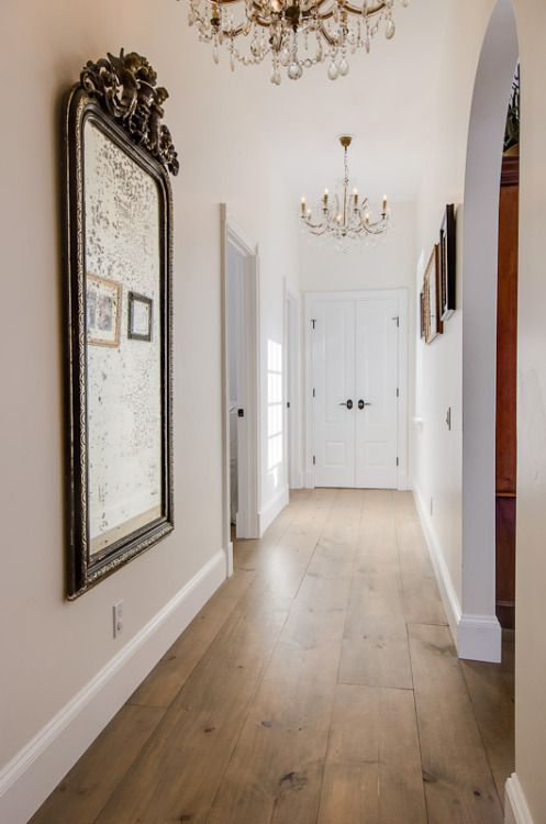 a chic entryway donen with neutral and warm hardwood floors, refined vintage mirrors and chandeliers