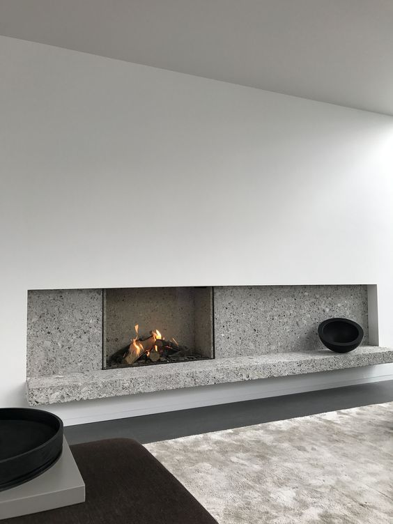 a minimalist fireplace with white paneling and grey stone plus some black touches for drama