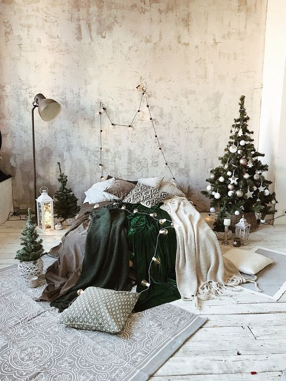 a neutral winter bedroom with a small Christmas tree decorated in white and silver, candle lanterns, green and white blankets