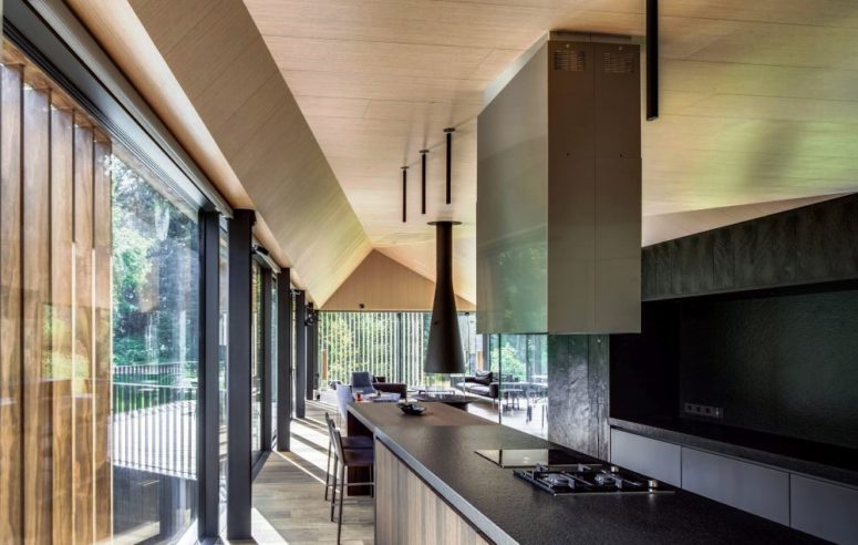 a black metal backsplash and a matching countertop help to create a minimalist and moody kitchen design