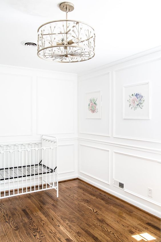 a gorgeous nursery with paneling, warm-colored hardwood floors and a beautiful chandelier