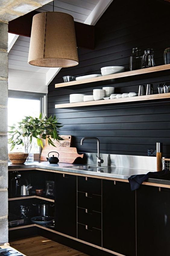 a black shiplap backsplash is a budget-friendly idea that matches the black plywood cabinets and a metal countertop