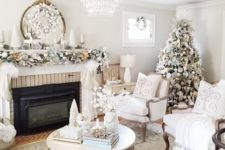 20 a refined neutral living room with a flocked Christmas tree, a garland with ornaments on the mantel and a snowy wreath