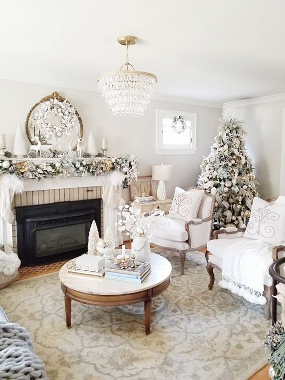 a refined neutral living room with a flocked Christmas tree, a garland with ornaments on the mantel and a snowy wreath