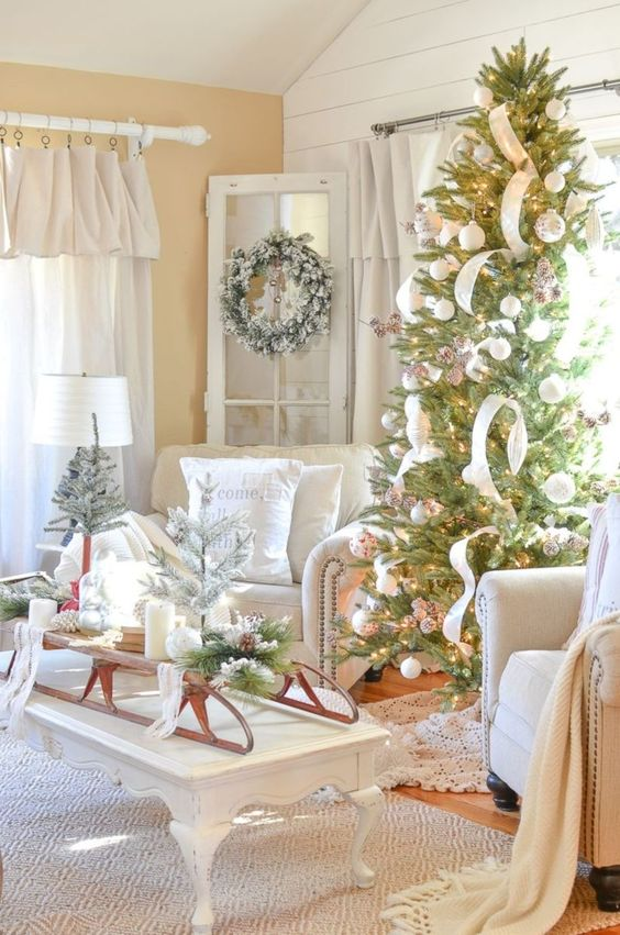 a sleigh with candles, pinecones, snowy evergreens, a snowy wreath with bells and a Christmas tree with white balls, pinecones and ribbons