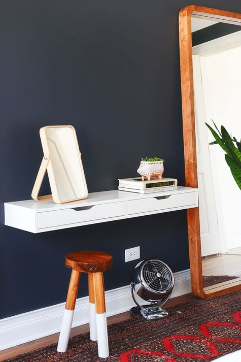 a small vanity made of an IKEA Ekby piece attached to the wall and a small natural stool with color blocked legs for a makeup nook