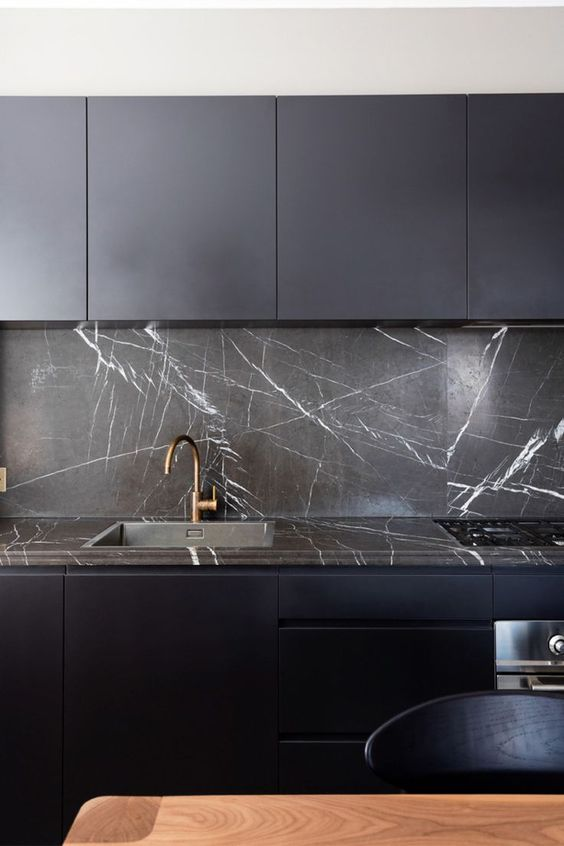 a minimalist midnight blue kitchen with sleek cabinets, black marble backsplashes and countertops plus brass fixtures
