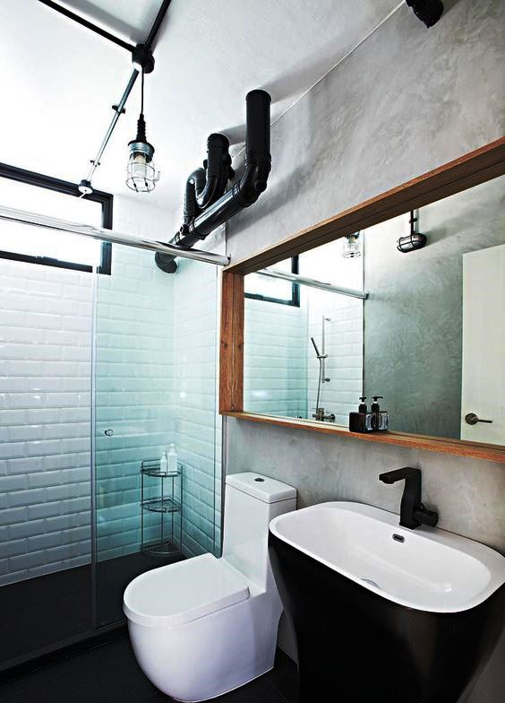 exposed metal pipes in the bathroom and industrial lamps make the space look cooler