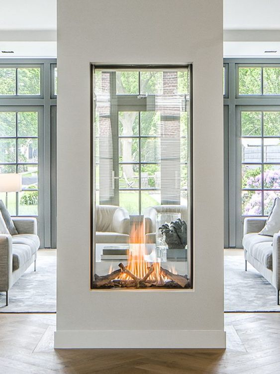 a large glass encased double-sided fireplace is a statement piece for any space