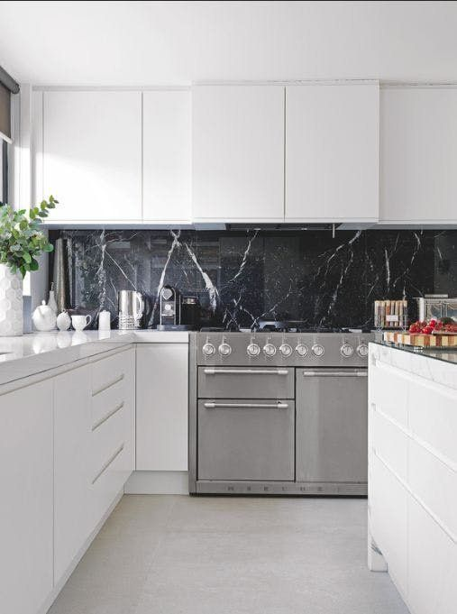 a pure white minimalist kitchen with a black marble backsplash that adds a refined and chic touch