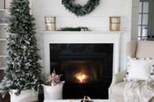 23 a snowy Christmas tree with pinecones and a matching wreath over the fireplace for clean and natural winter decor
