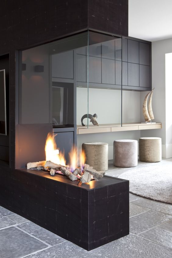 a dark tile clad fireplace with a glass hood is a super spectacular and refined idea for your home