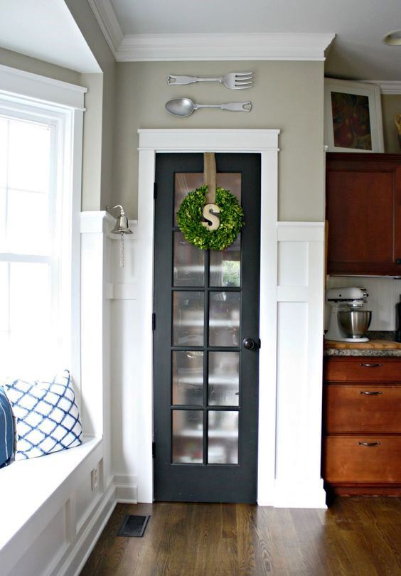 a mini built-in pantry with a graphite grey French door and a greenery wreath for a farmhouse kitchen