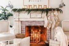 24 cozy winter fireplace styling with white candles, a greenery garland and candles, stockings, white pillows