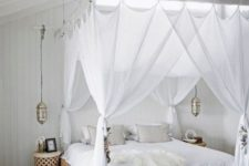 24 sheer white curtains match the white boho bedroom and hanging Moroccan lamps continue the decor theme
