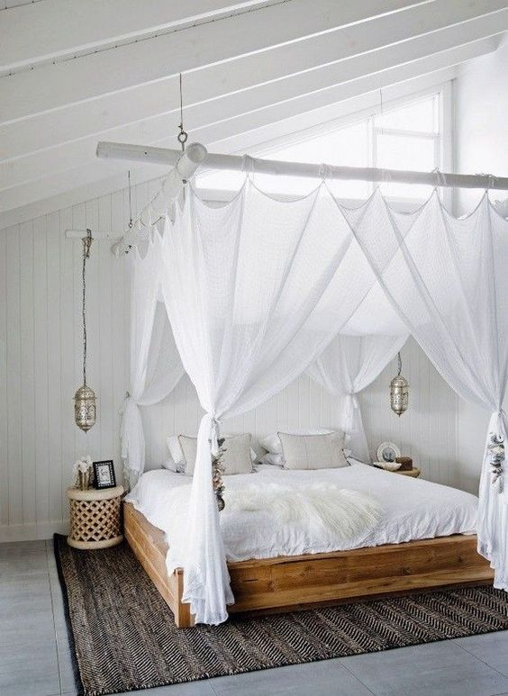 sheer white curtains match the white boho bedroom and hanging Moroccan lamps continue the decor theme