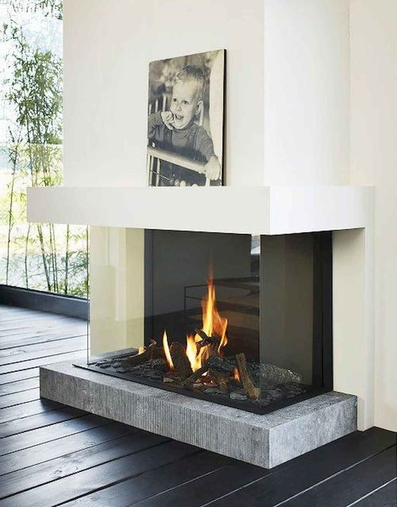 a modern fireplace with a concrete platform encased in glass is a very chic and refined idea with a modern feel