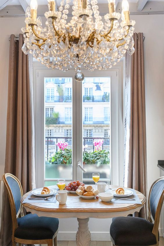 make your breakfast nook ultimately elegant with a large vintage crystal chandelier and chic furniture