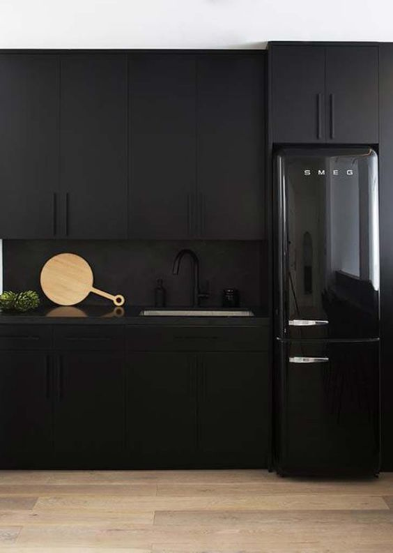 matte black cabinets, a matte black backsplash and a black shiny fridge for an edgy moody kitchen
