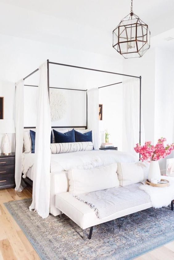 style your canopy bed with simple flowy white curtains for some privacy and to make the space cozier