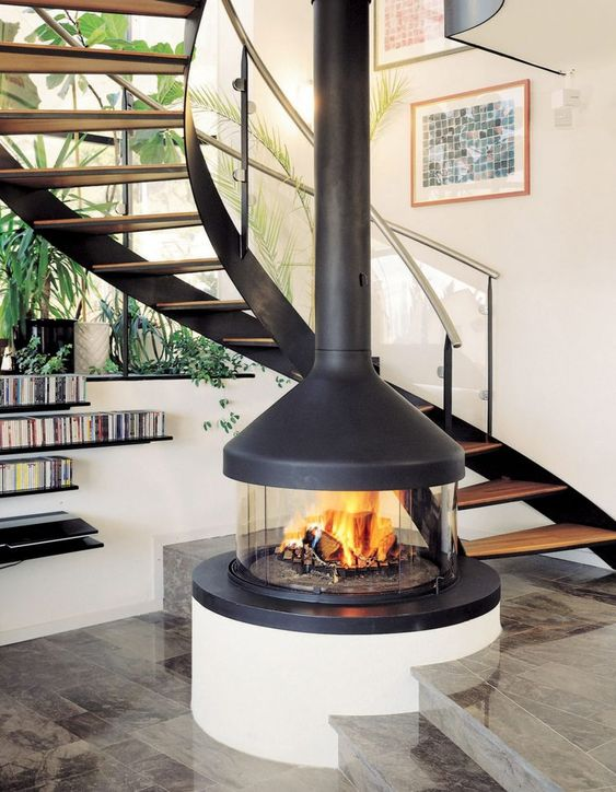 a stylish and cute glass encased fireplace with a dark metal hood will cozy up any space and highlight your staircase