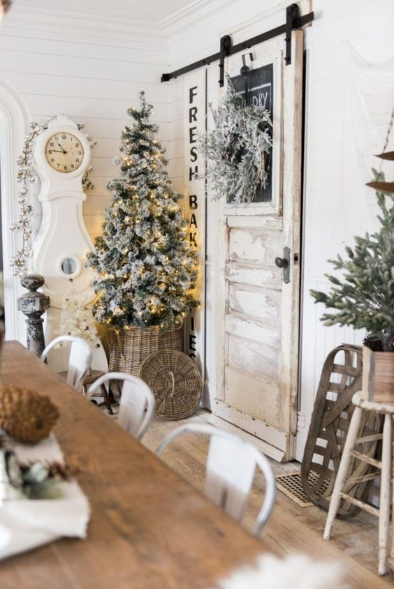 neutral farmhouse dining room decor with evergreens, a flocked Christmas tree with lights, an ornament garland and a basket