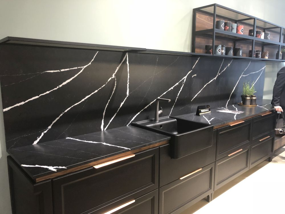 vintage inspired black cabinets with black stone countertops and a backsplash is a very refined and chic idea