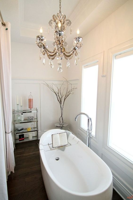 a contemporary bathroom made chic with a vintage crystal chandelier over the bathtub