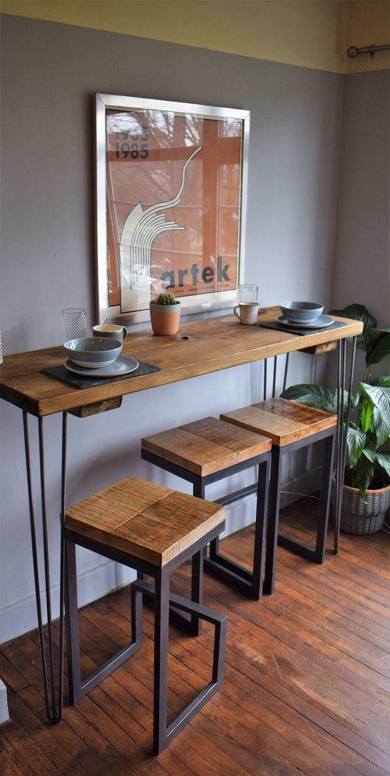 a tall industrial console table on hairpin legs and matching tall stools of wood and metal