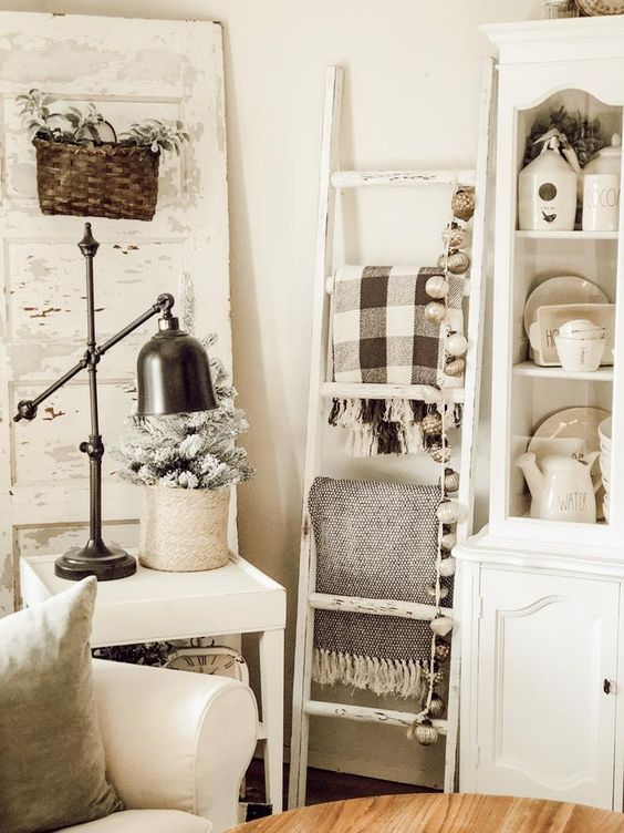 a white ladder with blankets and lights will easily fill in an awkward book giving you storage space
